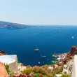 View of Fira town - Santorini island,Crete,Greece. White concrete staircases leading down to beautiful bay with clear blue sky and sea — Stock Photo