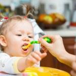 Child girl eats porridge — Stock Photo