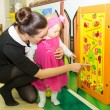 Stock Photo: Mom teaches his daughter child to figures in games room