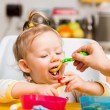 Child girl eats porridge from a spoon on kitchen. Use it for child, healthy food concept — Stock Photo #42449827