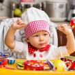 Stock Photo: Baby cook girl wearing chef hat in kitchen.  Use it for child, healthy food concept