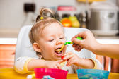 Child girl eats porridge from a spoon on kitchen. Use it for child, healthy food concept — Stok fotoğraf