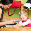 Mother and child girl drawing together with color pencils in preschool at the table in kindergarten — Stock Photo