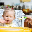 Child girl eats porridge from a spoon on kitchen. Use it for child, healthy food concept — Stock Photo
