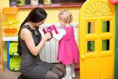Ragazza madre e bambino giocando all'asilo in classe scuola dell'infanzia montessori. — Foto Stock