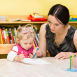Mother and child girl playing in kindergarten in Montessori preschool Class. — Stock Photo #48256831