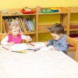 Two little kids drawing with colorful pencils in preschool at the table. Little girl and boy drawing in kindergarten — Stock Photo