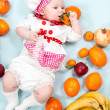 Baby girl with fruits. — Stock Photo