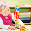 Little child girl playing with toy letter and number blocks  in kindergarten in Montessori preschool Class. — Foto Stock #48257763
