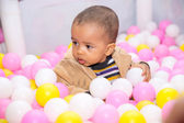 Happy black boy in colored ball on birthday on playground. The concept of childhood and holiday — Foto de Stock