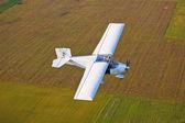 Een vliegtuig vliegen boven de velden — Stockfoto