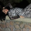 Latin model lying on stone fence — Stockfoto
