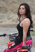 Beautiful brunette biker girl on the bike — Stock Photo