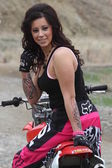 Beautiful brunette biker girl on the bike — Stok fotoğraf