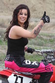 Tattooed biker woman sits on a motorcycle and showing thumbs up — Stock Photo