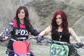 Two beautiful brunette biker girls  on the bikes — Stock Photo