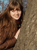 Young girl with dark hair and brown coat standing near a tree — Stock Photo