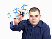 Young man in a blue shirt marker drawing a dollar sign — Stock Photo