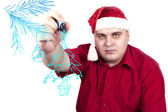 Young man in a red shirt and hat of Santa Claus, a Christmas tre — Stock Photo