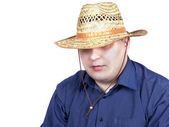 Young man in a blue shirt with a straw hat in hand — Stock Photo