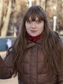 Ung flicka med mörkt hår i en brun kappa — Stockfoto