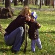 The young woman walks with the baby in park.Anamorphic wide-screen — Stock Video
