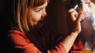 The little girl plays with a doll of an angel. Sequence of shots — Stock Video