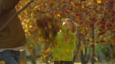 Sequence of slow motion shots happy mum and the little girl throw autumn leaves. — Stock Video