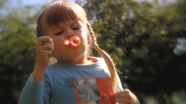 Sequence of soft focus shots. Little child enjoys blowing soap bubbles — Stock Video