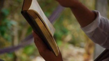 男は、熱帯の島の海岸で本を読みます — ストックビデオ
