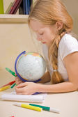 Little girl with blond hair examines globe — Stock Photo