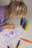 The little girl with blond hair draws — Stock Photo