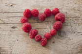 Some raspberries in a heart shape — Stock Photo