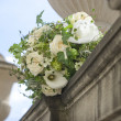 Stock Photo: Bouquet of white roses lying on an old fence