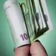 Man's hand with euro on green background — Stock Photo