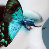 Beautiful woman eye close up with butterfly wings — Stock Photo
