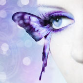 Beautiful woman eye close up with butterfly wings — Stockfoto