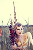 Schöne Frau in einem Blumenfeld — Stockfoto