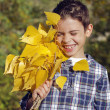 Smiling boy with yellow leaves — Photo