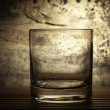 Glass back lit with grunge background — Stock Photo
