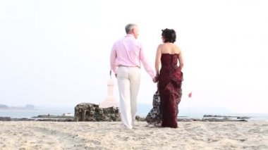 Couple walk along the beach — Stock Video