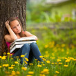 Tired school girl in the park with books — Стоковая фотография