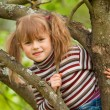 Stock Photo: Funny lovely little girl posing sitting on a tree in the garden
