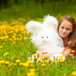 Young little girl holding a soft toy in the park, looking at camera. - Stok fotoğraf