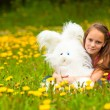 Young little girl holding a soft toy in the park, looking at camera. — Lizenzfreies Foto