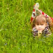Little five-year girl lying in grass. — Stock fotografie