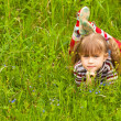Little five-year girl lying in grass. — Stockfoto