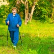 Foto Stock: Active old woman (85 years old) nordic walking outdoors.