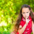 Young girl with her finger over her mouth, hushing. — Stock Photo #12432796