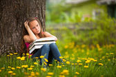 Tired school girl in the park with books — Stock Photo